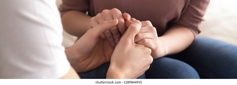 Panoramic close up image couple sitting on couch man holding hands beloved woman, gesture empathy support, symbol sincere feelings declaration of love horizontal photo banner for website header design