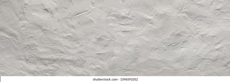 Panoramic closeup of a bright wall with abstract rough plaster structure