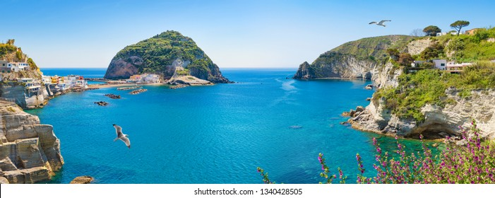 Panoramic collage with green rocky coast and giant green rock in azure sea near near small village Sant'Angelo, Ischia Island, Italy.