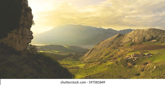 Panoramic colorful toned landscape with a beautiful mountains, powerful cloudy sky and green valley.