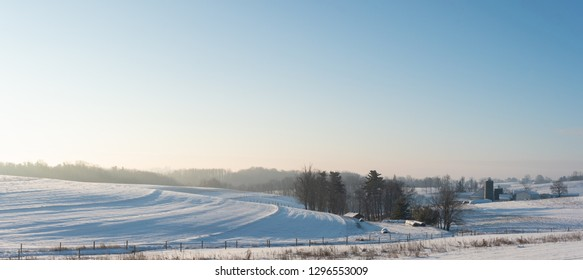 Panoramic country background of snow-covered farmland and barn and silos at sunrise in rural Appalachia.