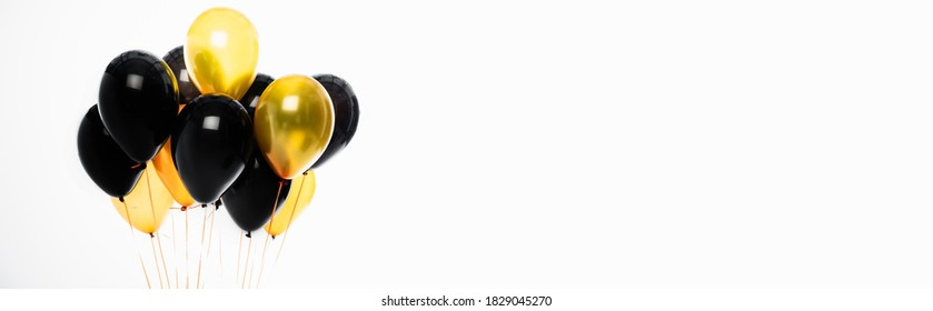 Panoramic crop of black and yellow balloons isolated on white with copy space