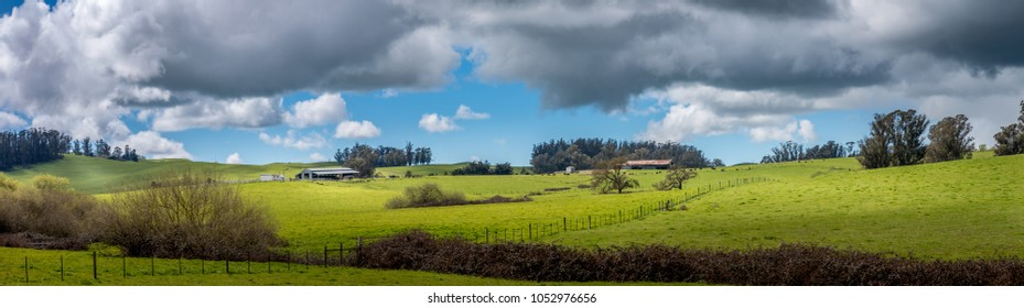 Panoramic of a dairy farm with a barn and green pastures. A blue sky with fluffy white clouds and threatening dark rain clouds are above. There are patches of sun and shadow on the green pastures.