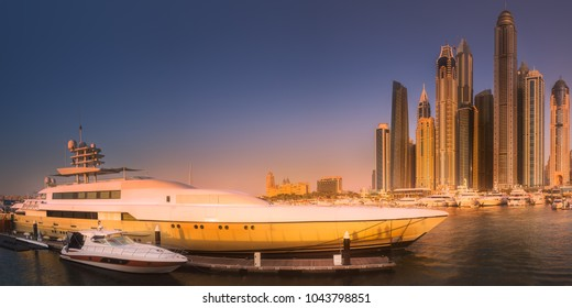 Panoramic day view of sea bay with yachts at sunset in Dubai Marina, UAE.