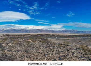 Panoramic desert scene showing ancient lava flows with a background of cloudy sky and mountains along route 66