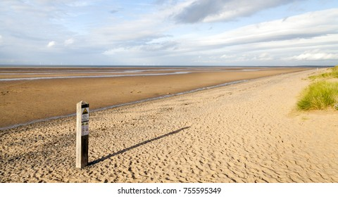 Panoramic Deserted Beach Scene in late afternoon with golden sand, long shadows grass, sea, sky,