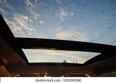 Panoramic double sunroof  in the interior of the car. View from blue sky