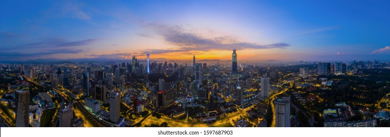 Panoramic drone aerial view of sunrise at Kuala Lumpur city skyline. Empty city lockdown coronavirus concept. Image may contain noise due to low light and high ISO setting.