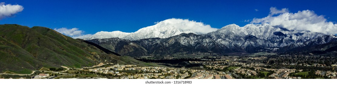 Panoramic, drone view of snow covered Mount San Gorgonio and the Little San Bernardino Mountains above Yucaipa Valley with white clouds, blue sky and green hills