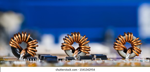 Panoramic electrotechnical background. Toroidal inductors with beautiful copper wire winding. Electronic components as coils or transistors on circuit board detail. Copy space on a blue blurry device.