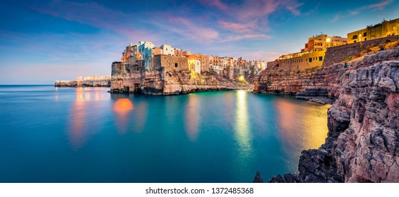 Panoramic evening cityscape of Polignano a Mare town, Puglia region, Italy, Europe. Amazing  spring sunrise view of Adriatic sea. Traveling concept background.