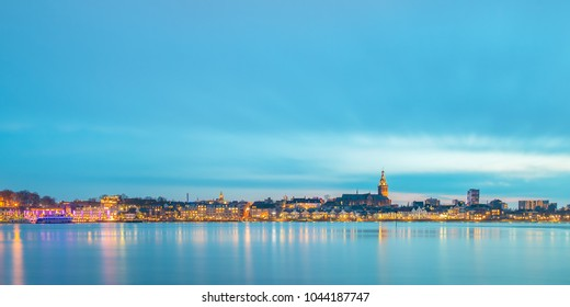 Panoramic evening view of the Dutch city of Nijmegen with the flooded river Waal in front