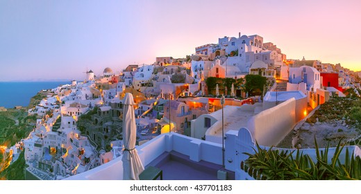 Panoramic famous view, Old Town of Oia or Ia on the island Santorini, white houses and windmills at dawn, Greece