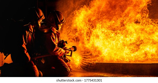 Panoramic firefighters using Twirl water fog type fire extinguisher to fighting with the fire flame from oil to control fire not to spreading out. Firefighter and industrial safety concept.