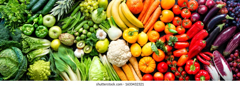 Panoramic food background with assortment of fresh organic fruits and vegetables in rainbow colors
