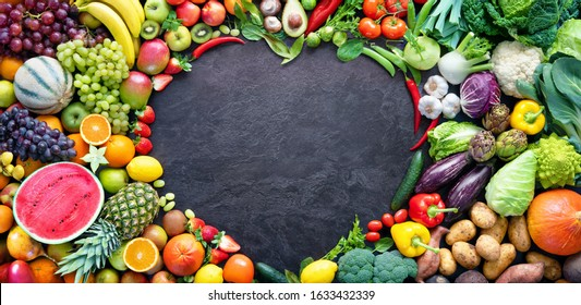 Panoramic food background with assortment of fresh organic fruits and vegetables. Copy space in heart shape
