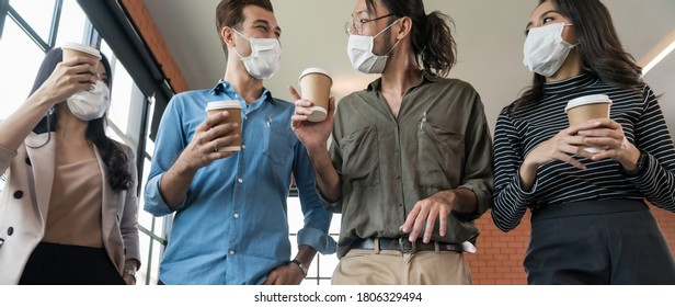 Panoramic group of business worker team with takeout coffee cup walking back to office after lunch break. They wear protective face mask in new normal office preventing coronavirus COVID-19 spreading.