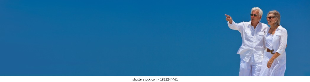 Panoramic happy senior man and woman couple walking together in bright clear blue sky, the man is pointing panorama web banner header