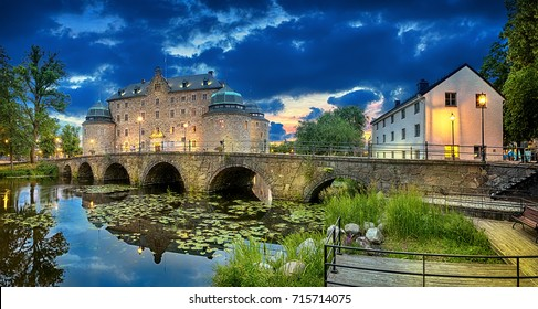 Panoramic HDR image of Orebro Castle and bridge reflecting in water of Svartan river at dusk, Sweden