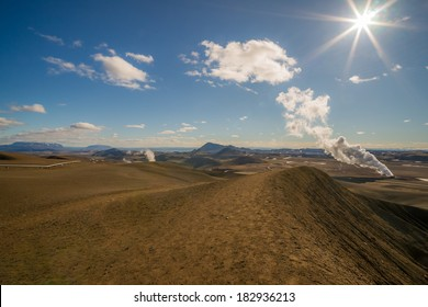 A panoramic icelandic landscape in the Krafla region with a steam volcano in the background at afternoon sun