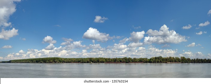 Panoramic image of beautiful blue Danube. Trees are on the other side of the river. Made from several frames stitched together to achieve very high resolution.