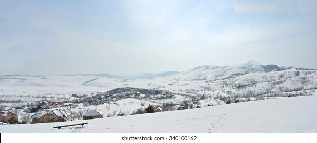 Panoramic image of beautiful, idyllic snowy winter landscape in the mountains, on a quiet morning, with snow-covered rooftops of a small picturesque village.