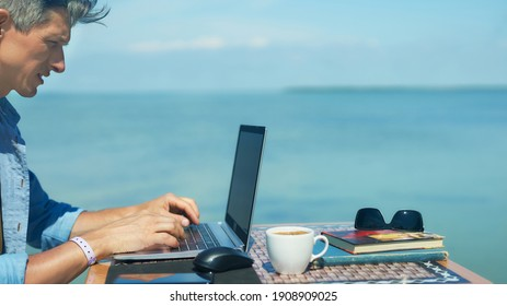Panoramic image businessman working outdoors by beautiful blue sea view , searching information on laptop computer, keyboarding text. Concept remote work and travel