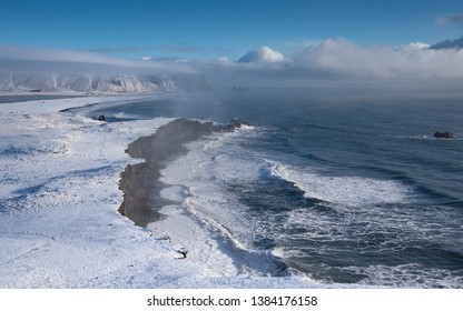 Panoramic image of the coastal landscape of Cape Dyrholaey on a winter day with snow-covered coastline, Iceland