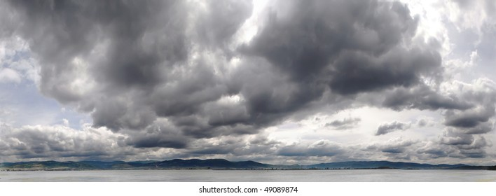 panoramic image of gray storm clouds over river