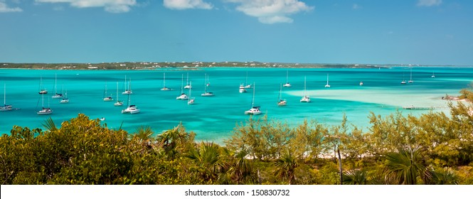 panoramic image of the harbour, or anchorage, in the bahamas near George Town in the Exumas.  Sand bar with small boat dock is off to the right and copy space is available in the clear blue sky