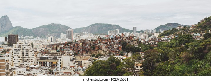 Panoramic image of Rio de Janeiro favelas district surrounded by hills and modern office and residential houses; a pronounced tendency towards social differentiation: poor buildings among regular ones