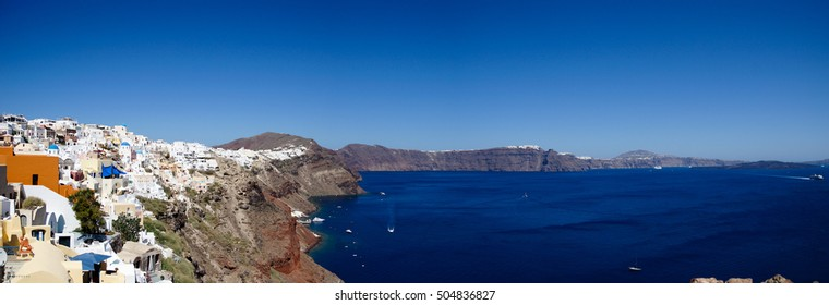 Panoramic image of the sheer cliffs and blue water of Santorini in Greece