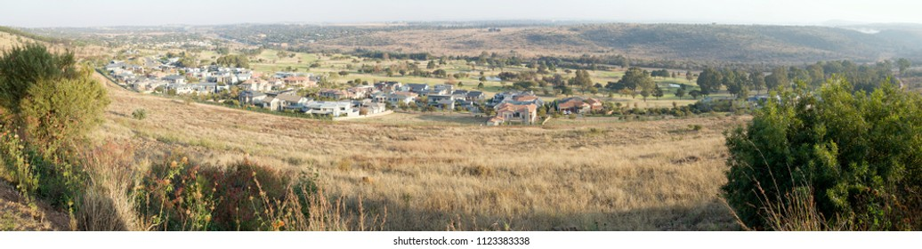 A panoramic image showing the affluent suburb of Waterkloof, Pretoria, South Africa.  There is a golf course next to the houses.