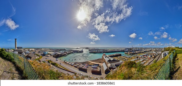 Panoramic image of St Helier Harbour with the town centre of St Helier, sea and blue sky with some clouds.