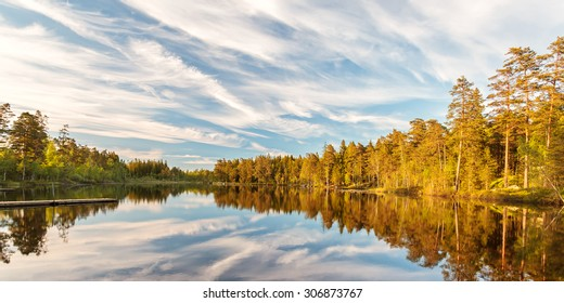 Panoramic image of tree reflections in a lake during early sunset in Smaland, Sweden