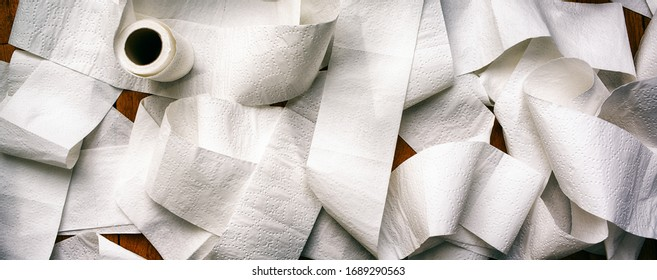 Panoramic image of unrolled white toilet paper lying on wooden table. Banner proportioned high resolution image.