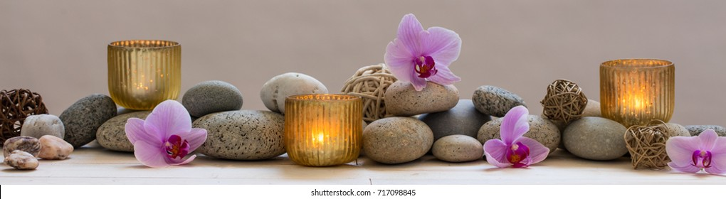 panoramic indulging still life for harmony and balance in spa, massage, yoga or feng shui with mineral pebbles, natural orchid flowers and candles