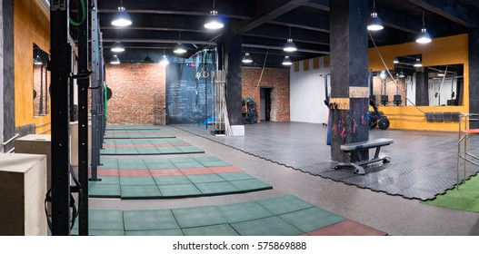 Panoramic interior of a fitness gym with trainers and sport equipment