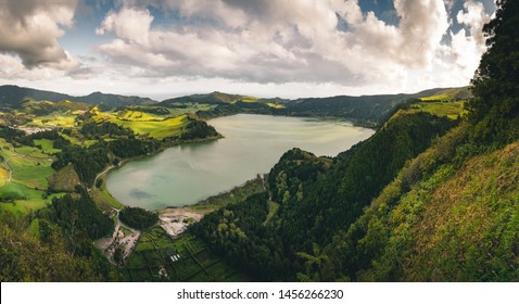 Panoramic landscape with aerial view on beautiful blue green crater lake Lagoa das Furnas and village Furnas with vulcanic thermal area. Sao Miguel, Azores, Portugal. Countryside landscape with green