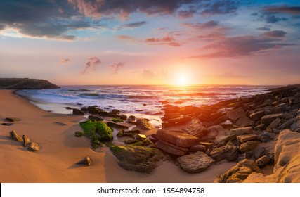 Panoramic landscape of amazing sunset on the ocean. View of dramatic cloudy sky and stony coast.  Portugal. Concept of harmony with wildlife.