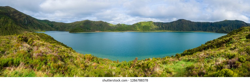 Panoramic landscape with beautiful blue crater lake Lagoa do Fogo from top of the hill on hiking trail. Lake of Fire is the highest lake of Sao Miguel island, surrounded by Natural Reserve green