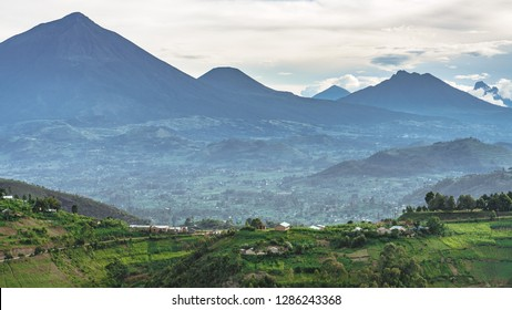 Panoramic landscape between virunga mountains in rd Congo and volcanoes national park in Rwanda. African landscape with local village road from Uganda border to Kabale