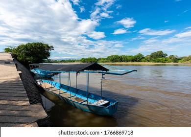 Paisaje panorámico con barco azul a orillas del río Magdalena. Neiva, Colombia.