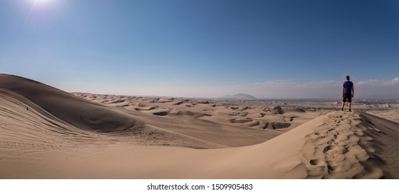 Panoramic landscape from a desert an a man standing alone over a dune on the right side. Ica, Peru