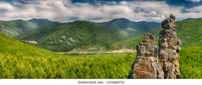 Panoramic landscape: a large rocky peak against the background of green mountains, hills and smaller rocks, a contrasting blue sky and clouds. HDR image with polarisation lens filter