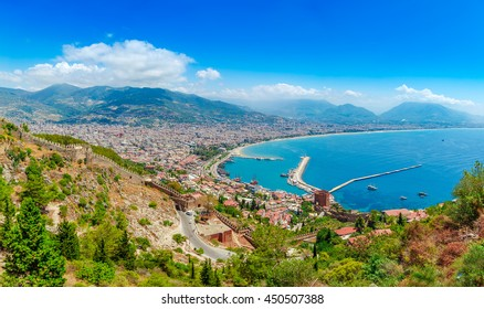 Panoramic landscape with marina and Kizil Kule tower in Alanya peninsula, Antalya district, Turkey, Asia. Famous tourist destination with high mountains. Part of ancient old Castle. Summer bright day