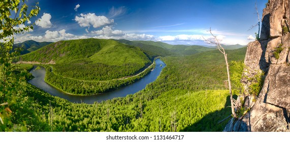 Panoramic landscape: mountain, river and rocks. The mountain river surrounds a mountain in a semicircle, overgrown with forest. Rocks on the right. Contrasting blue sky and clouds. HDR polarization