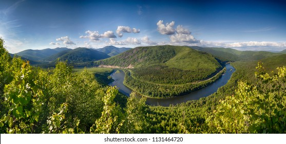 Panoramic landscape: the mountain river surrounds a mountain in a semicircle, overgrown with forest. A contrasting blue sky and clouds. HDR image with polarisation lens filter