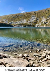 Panoramic landscape on Golemo Ezero(Big lake) on Baba Mountain, National park Pelister- Pelisterski Oci - perfect water reflection on rocky mountain reflected in the lake and white dog - Shutterstock ID 1819557029
