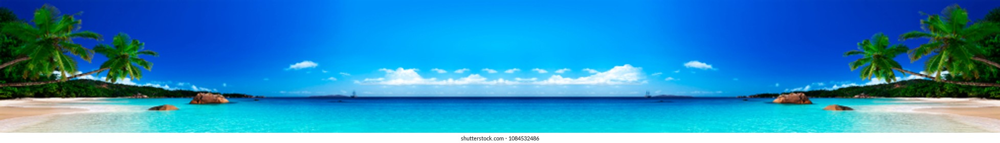 Panoramic landscape of the sea and the beach with small ships in the background.
